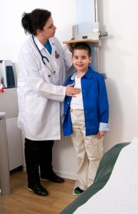 Pediatric nurse taking height of child