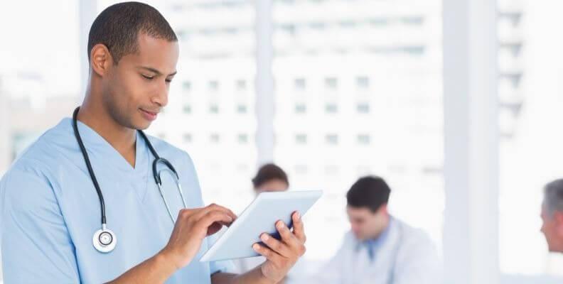 Male Nurse Documenting on Tablet