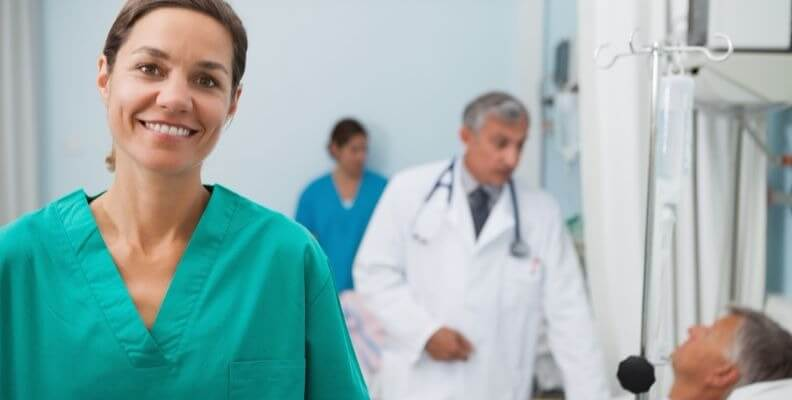 Nurse in Foreground and Doctor with Patient in Background