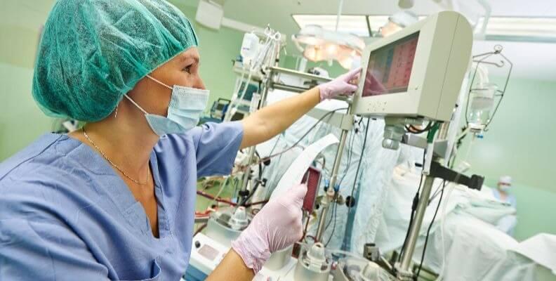 Operating Room Nurse Adjusting Monitors