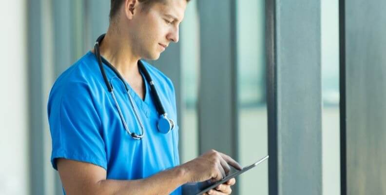 Male Nurse Using Tablet to Document