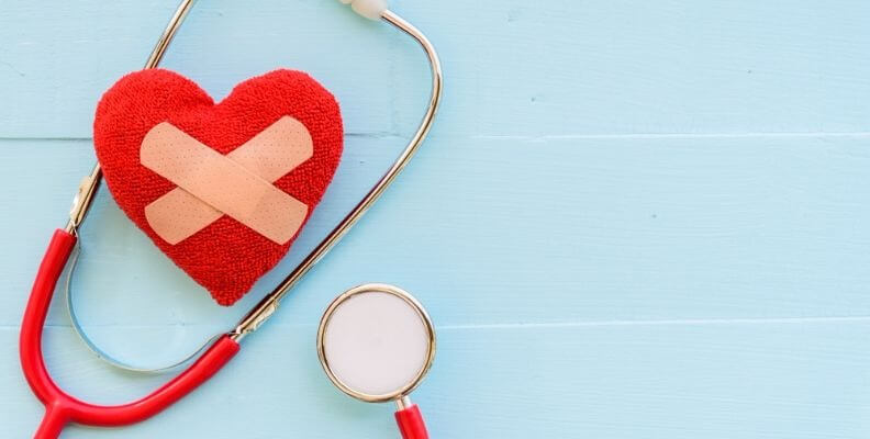 Stethoscope wrapped around a heart patch with bandages on it