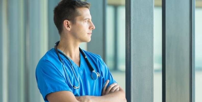 Male Nurse Looking out Window